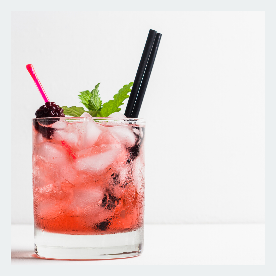 fruity cocktail on the rocks with straw and mint leaf