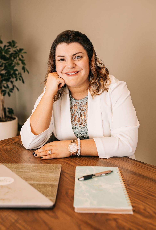 Krysti sitting at table wearing white jacket
