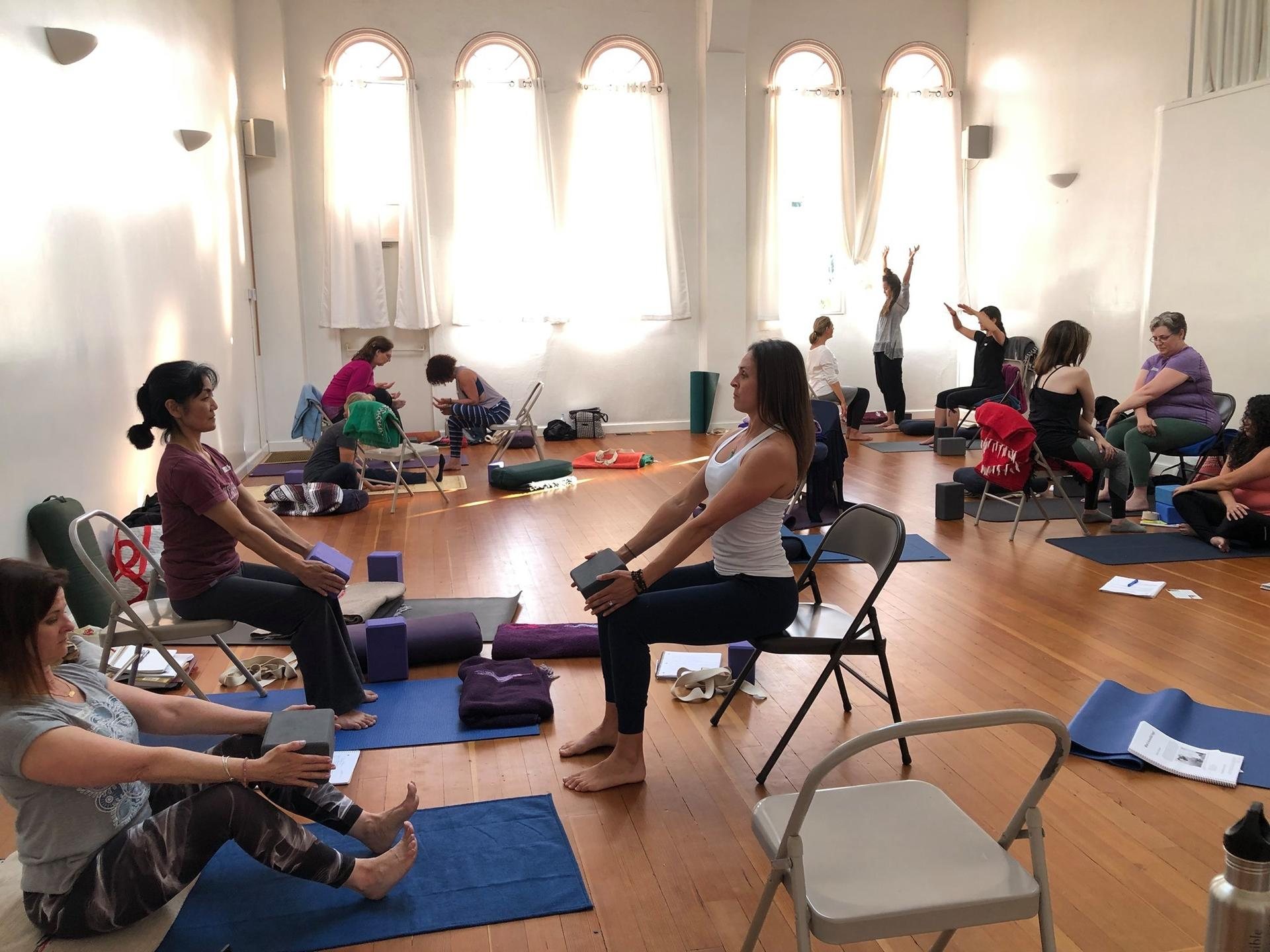 Photograph of students taking an in-person Accessible Yoga Training