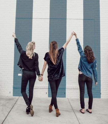 three women holding hands celebrating with their backs to the camera