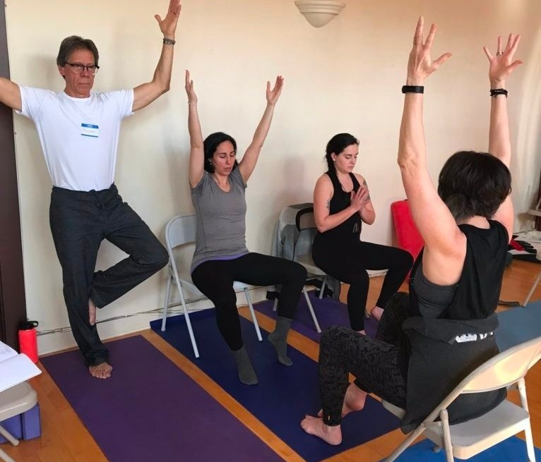 Photograph of 4 yoga teachers practicing together at the Accessible Yoga Training Intensive