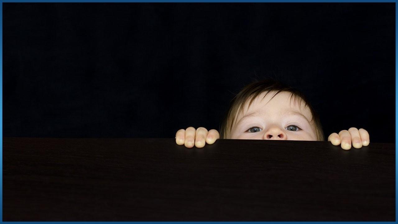 little baby peeking over object