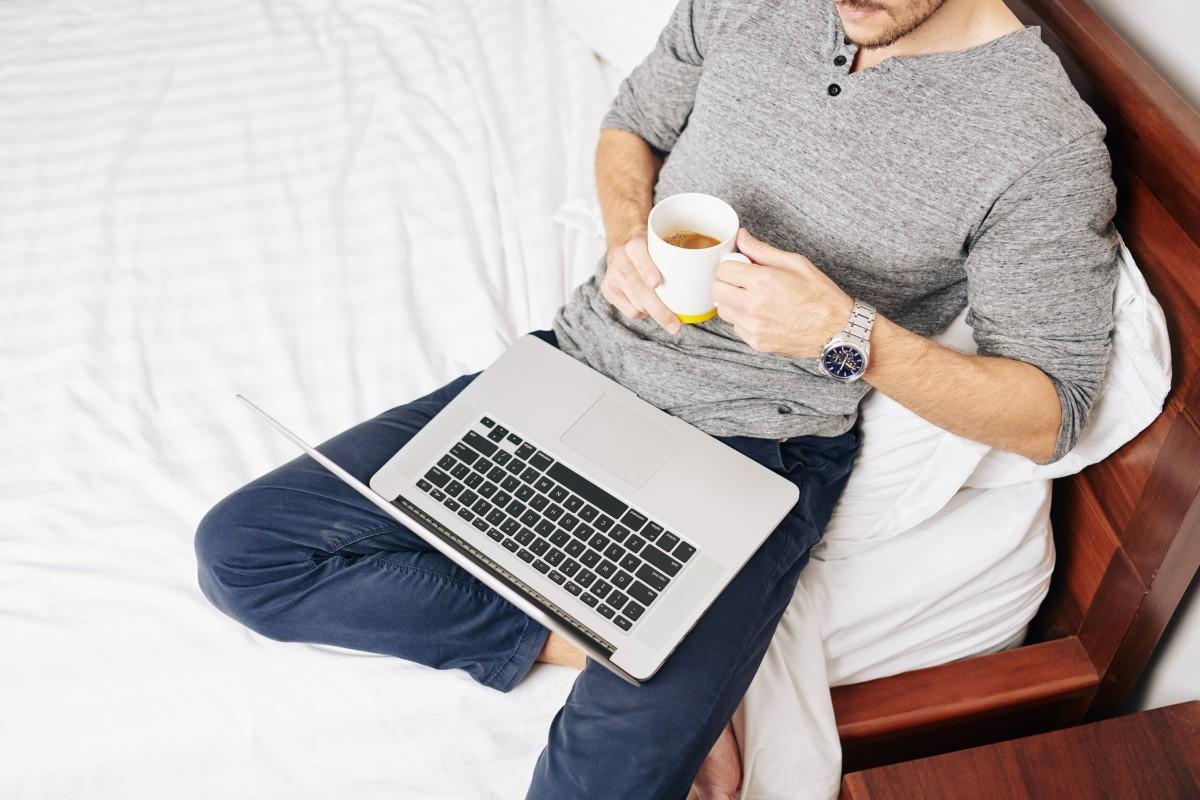 man watching a virtual workshop on his laptop in bed while drinking coffee