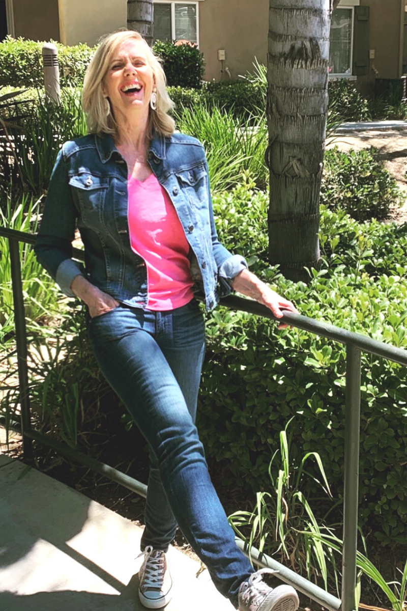 Lori Massicot, woman standing outside laughing in blue denim and pink shirt