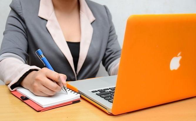Woman taking notes on her notebook while listening an online workshop on her orange laptop