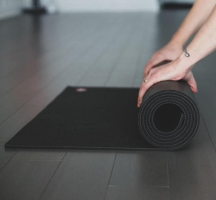 Unrolling of black yoga mat