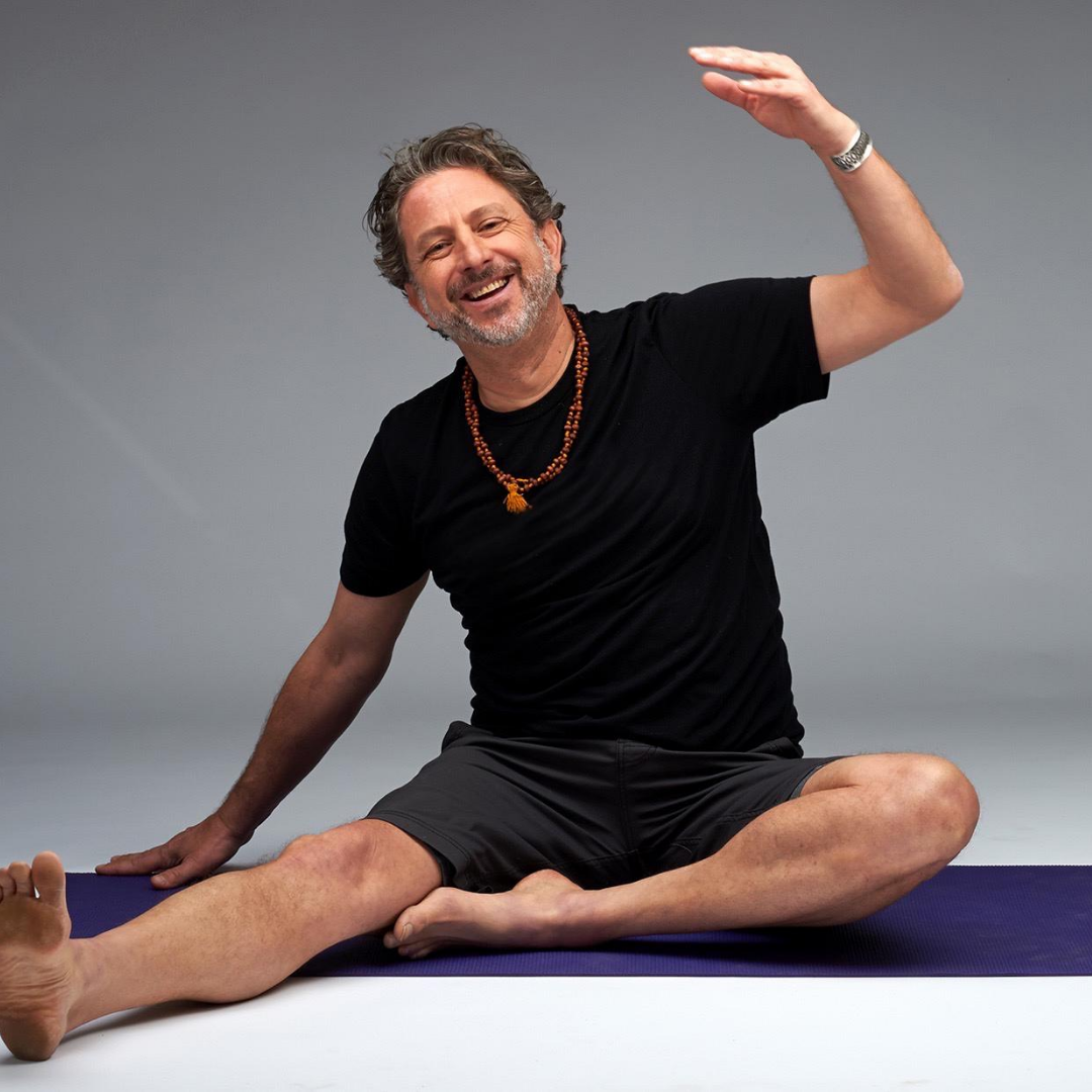 brad wetzler male yoga teacher smiling on mat