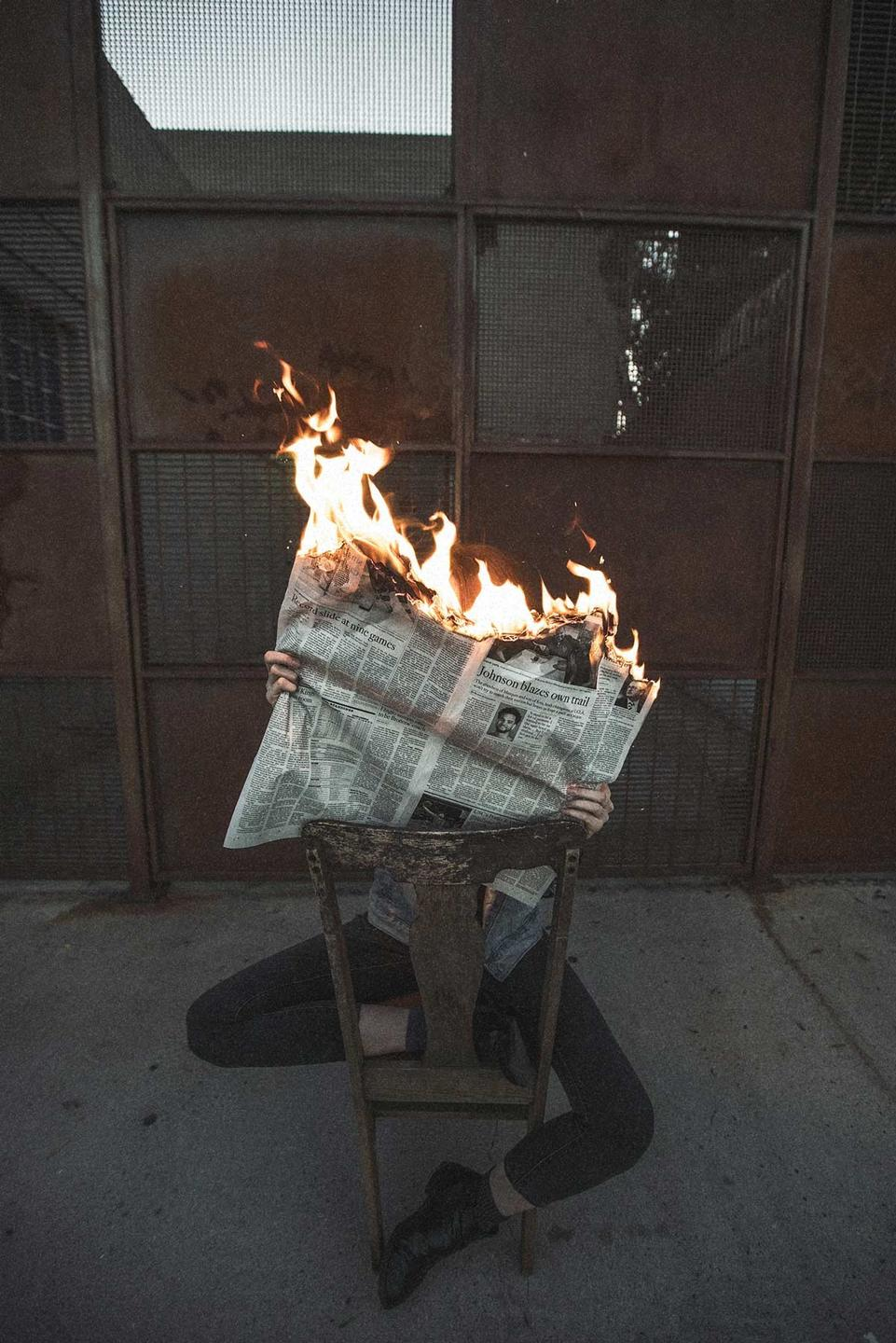 Person reading a newspaper that's on fire