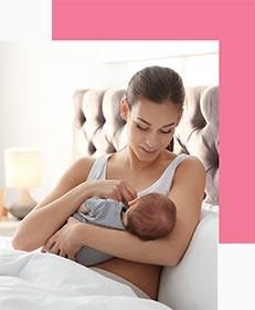 Mother Breastfeeding her Baby In Bed