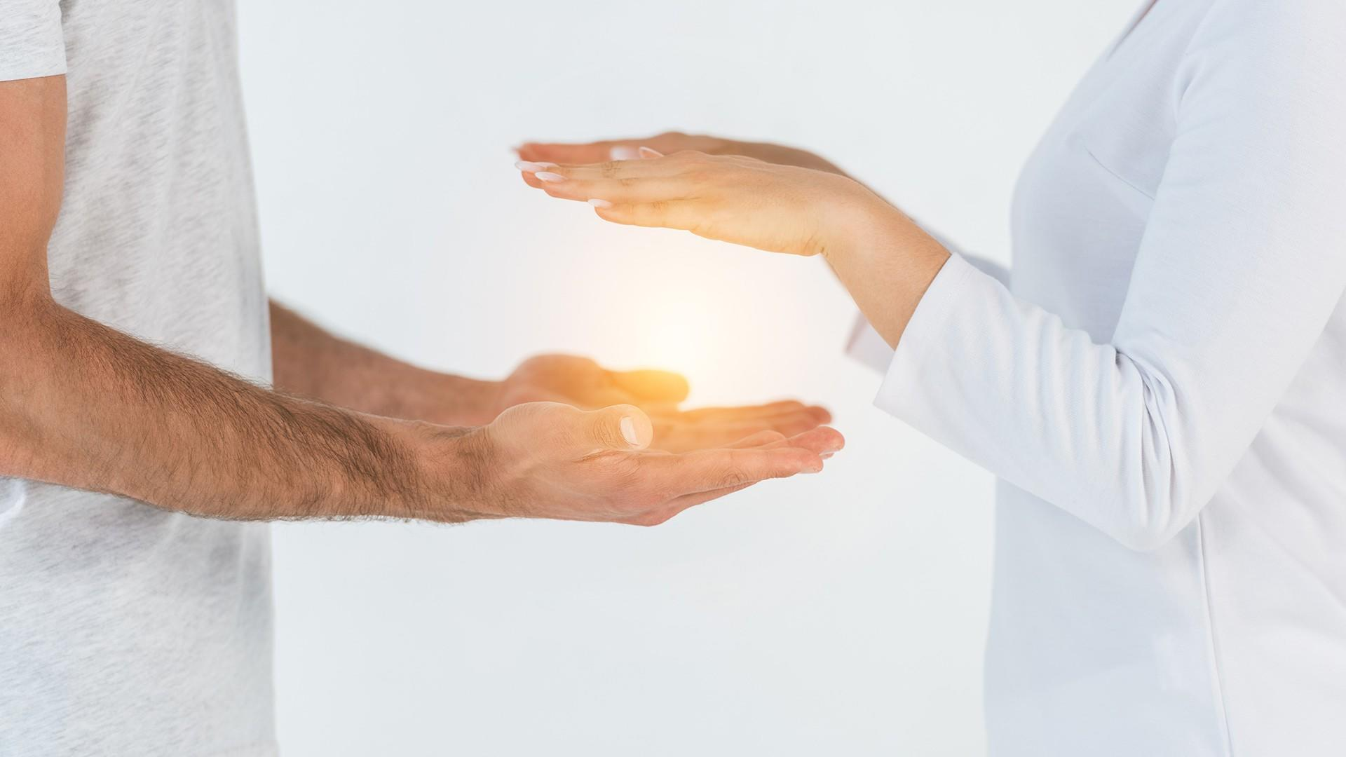 female hands hovering over male hands with energy in between - Energy Medicine Services available at pureBalance Wellness