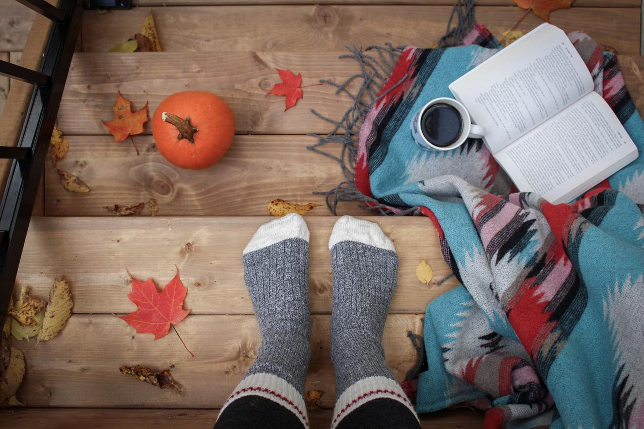 Cozy, fall porch scene with socks, a blankie, some coffee and a good book