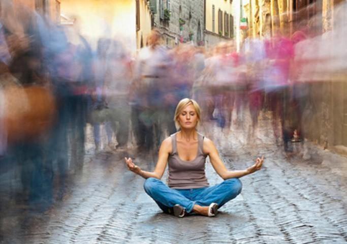 woman meditating crowded street