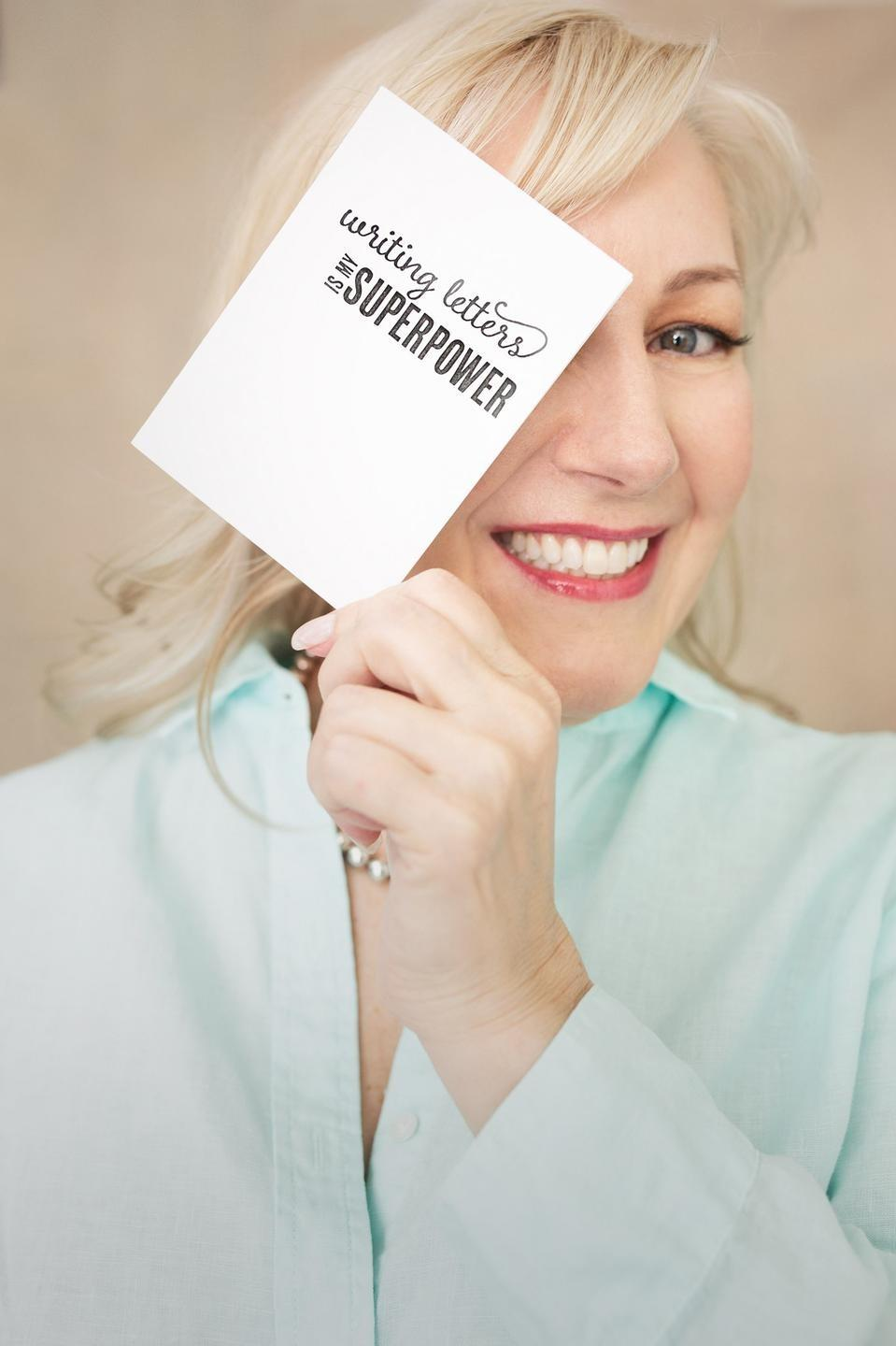 Beth Ann smiling and holding a note card.