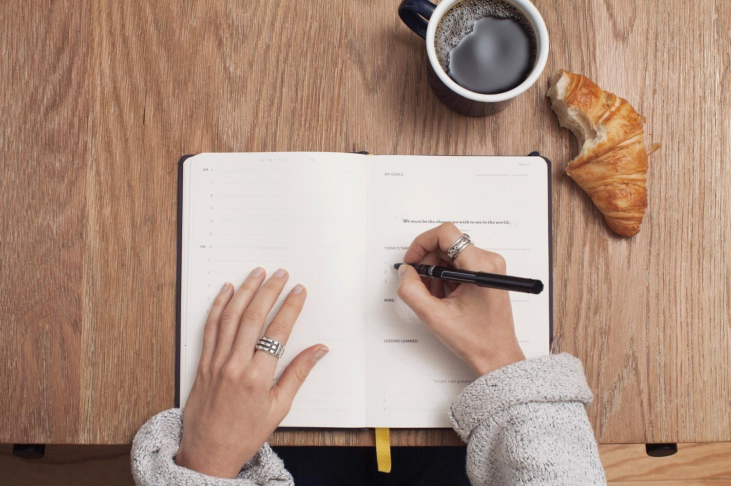 womans hand writing in journal with coffee and croissant