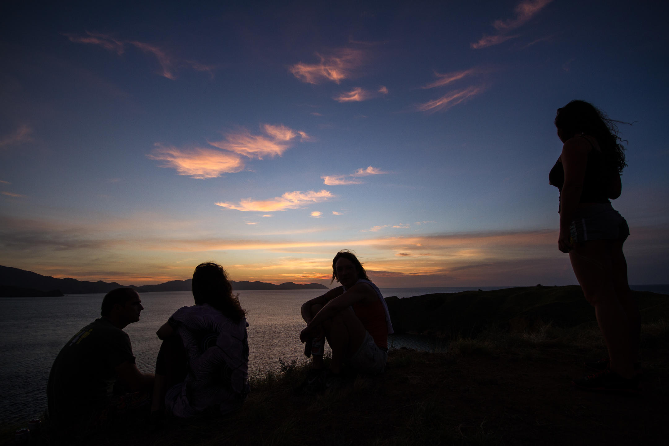 Four friends silhouetted as they watch the sunset