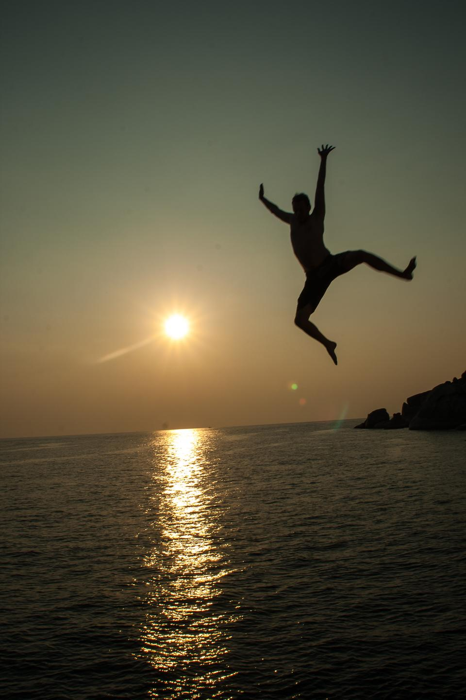 a silhouette of a man jumping from a boat shortly before the sun sets