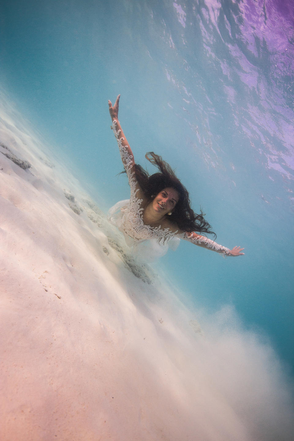 A bride free diving in her wedding dress for some extra special wedding photos
