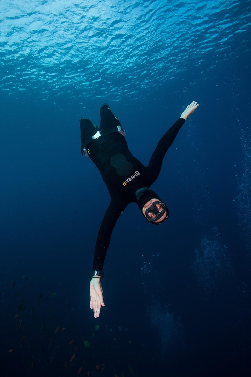 A free diver on descent with arms open