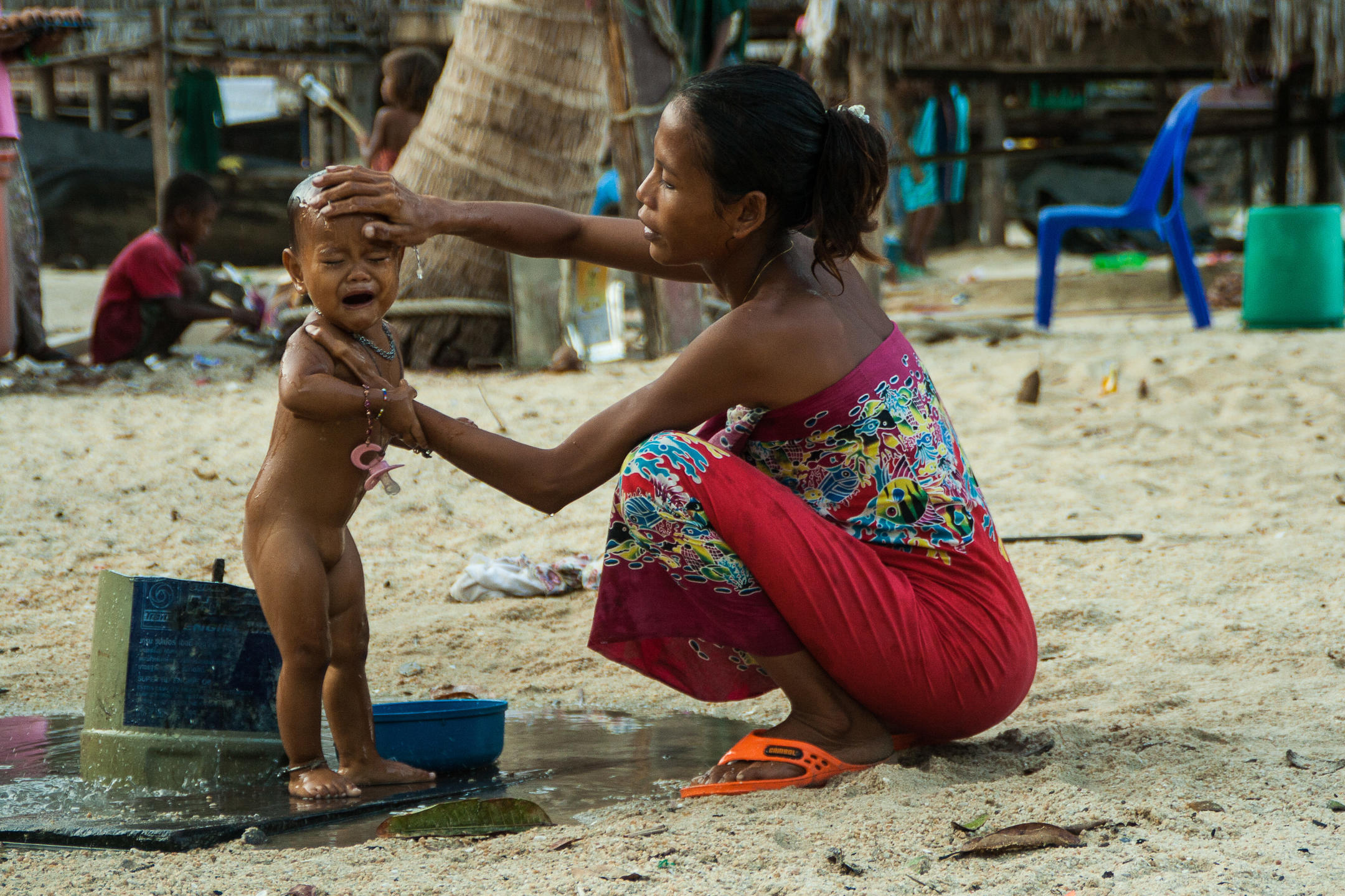 A mother washing her baby in a sea gypsy village in Thailand