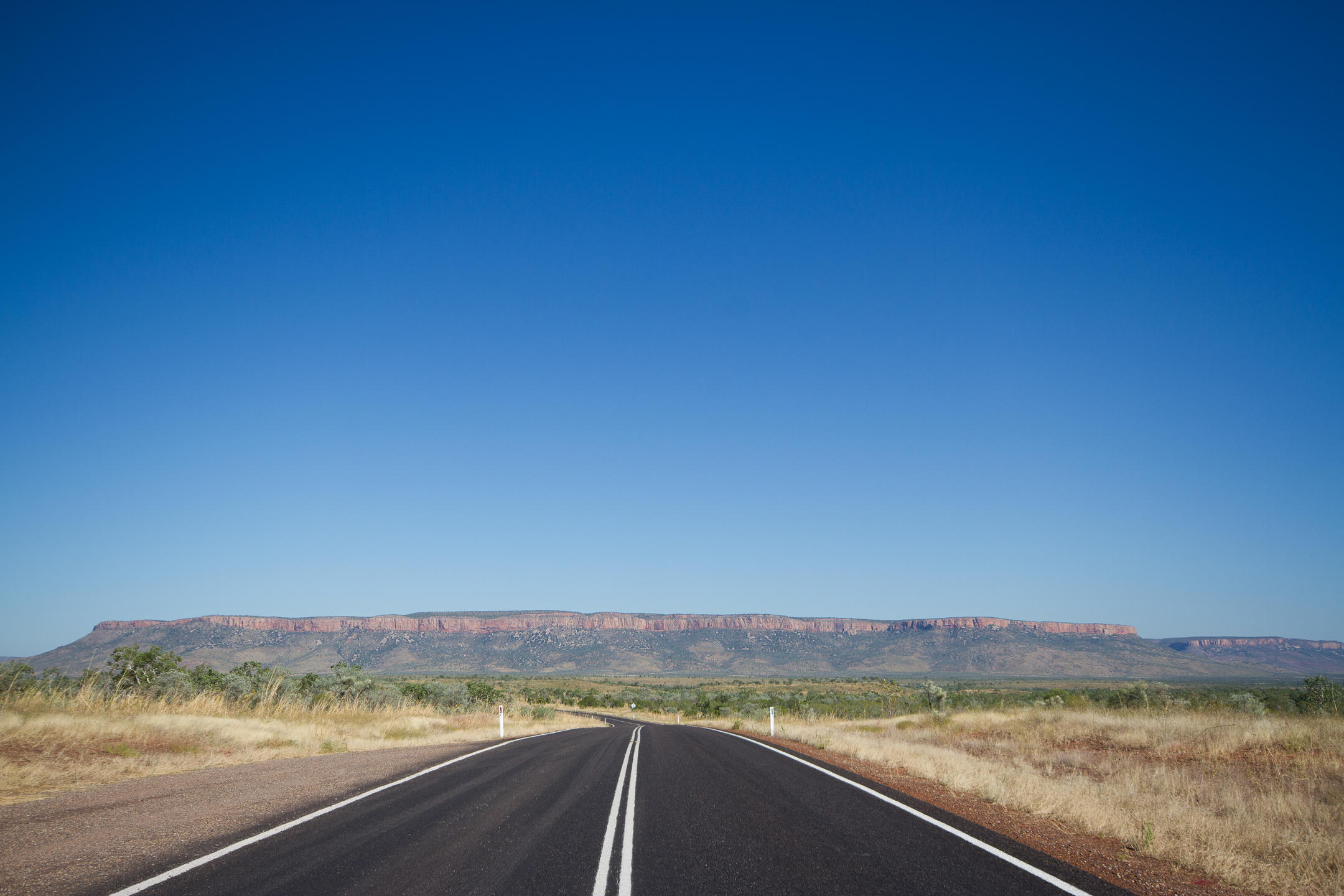 An empty road leading to mountains in the distance
