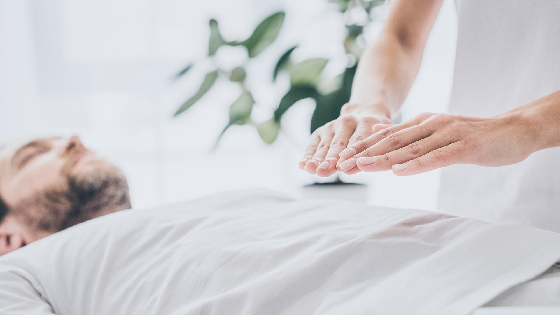 woman holding hands above a man's abdomen - Therapeutic Touch Services are available at pureBalance Wellness in Mississauga