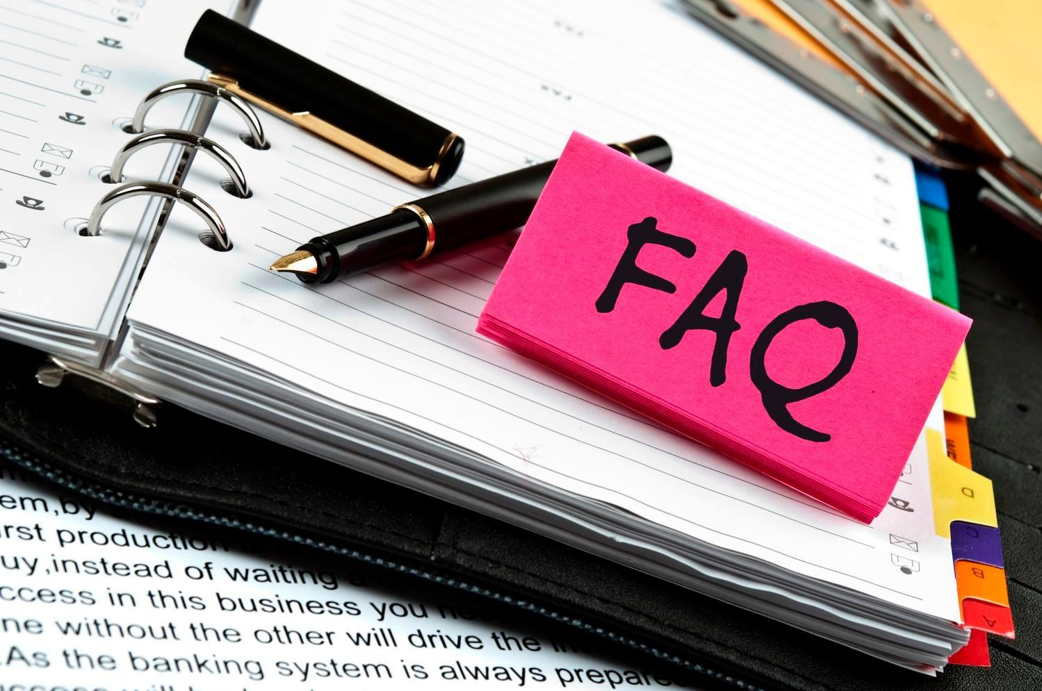 FAQ Sign Sitting on Planner