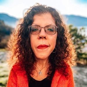 Linn Kleppa er åndelig veileder. Dette er et bilde av henne med oransje, strikket cardigan, svart t-skjorte og rød leppestift. Håret er løst og krøllete, og været er nydelig.