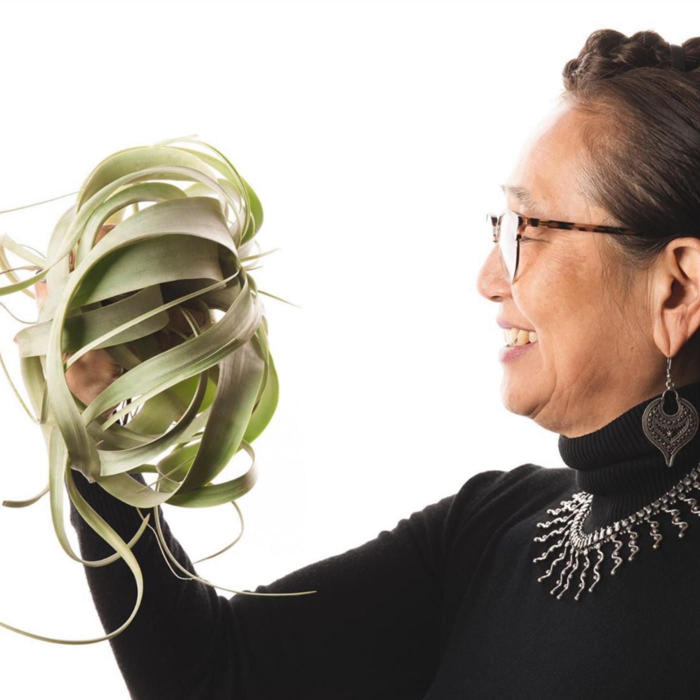 Hitomi Gilliam floral designer and educator smiling holding a succulence for Viva La Flora Live Podcast