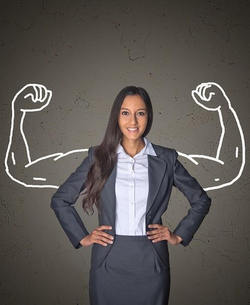 Asian woman in business suit with a shadow in the shape of super woman