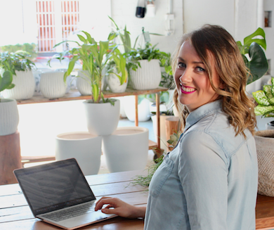 Em Pescott at desk with greenery in background
