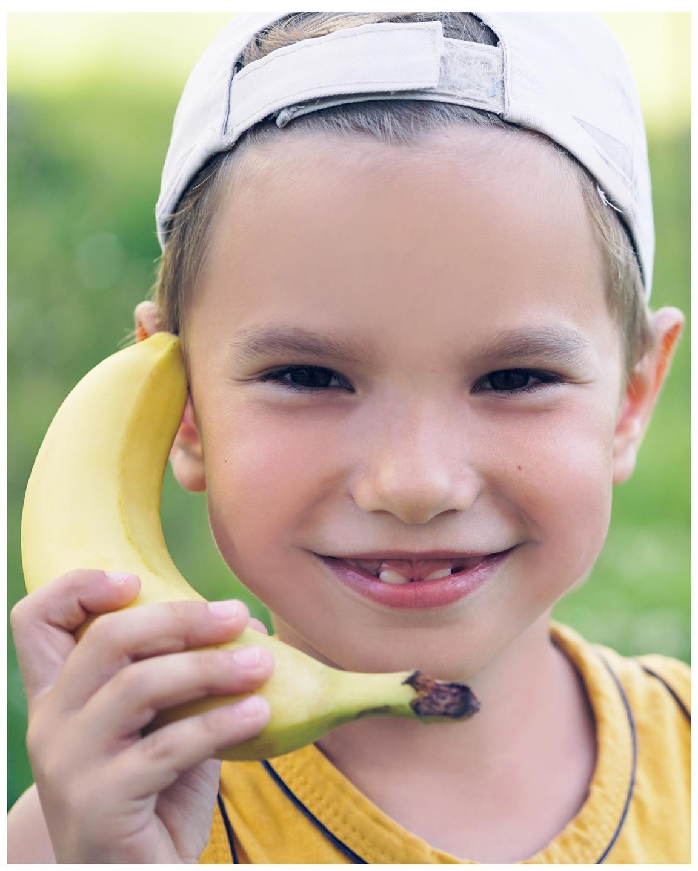 Child using a banana like a telephone