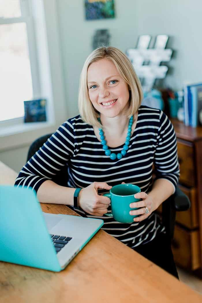 Picture of Stacey Nachajski sitting at desk with laptop and teal mug