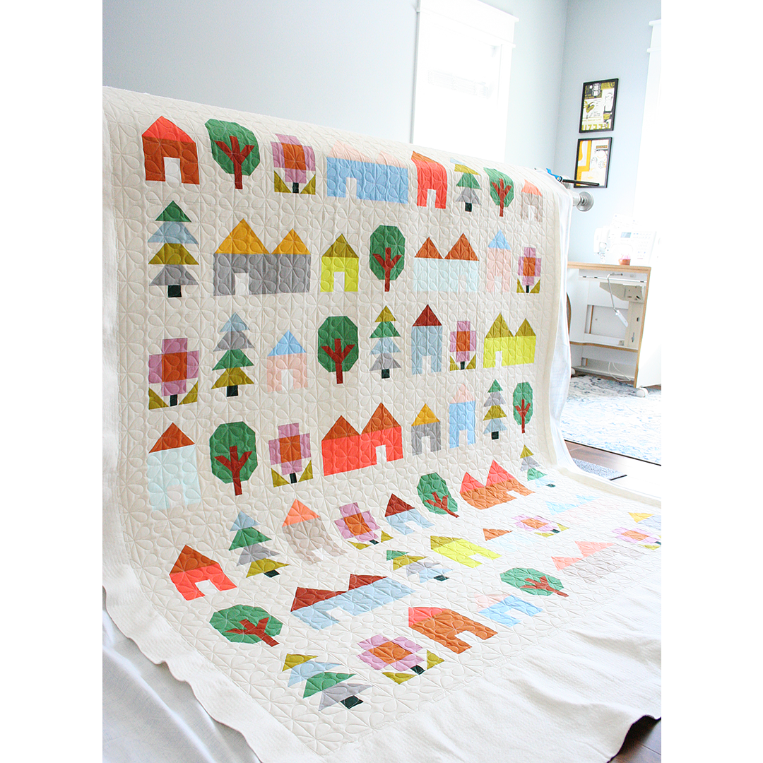 Quilt draped over a longarm frame showing blocks made of houses and trees