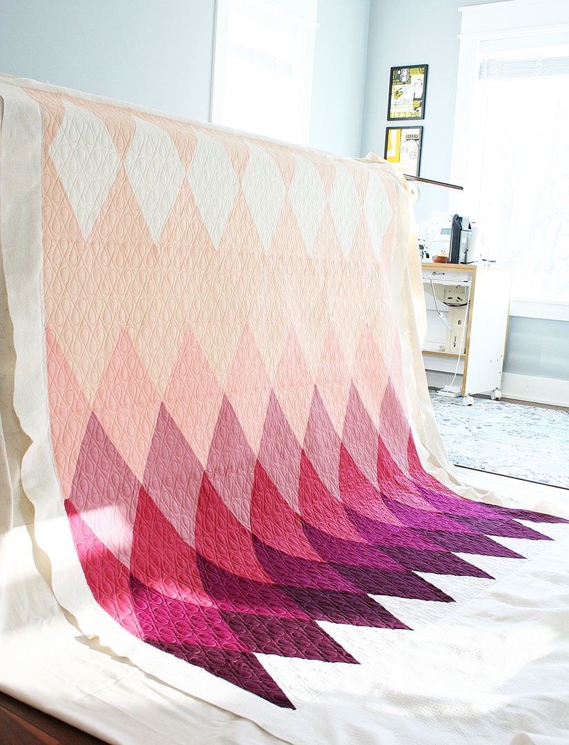 Quilt draped over a longarm quilting frame showing solid diamonds in a pale peach to dark purple scale.