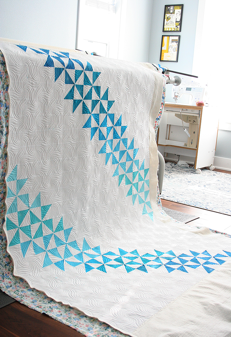White quilt draped over a longarm quilting frame with pieces of bright blue and distinctive quilting.