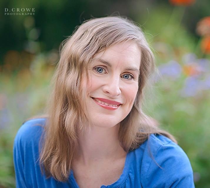 woman in blue shirt sitting in field of flowers