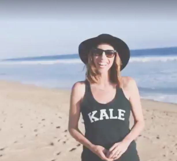 woman in floppy hat standing on beach