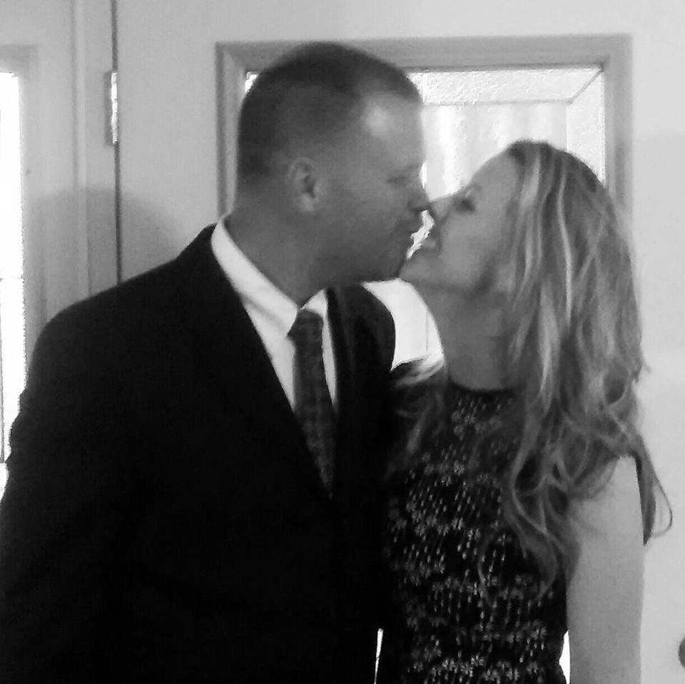 husband and wife kissing near door