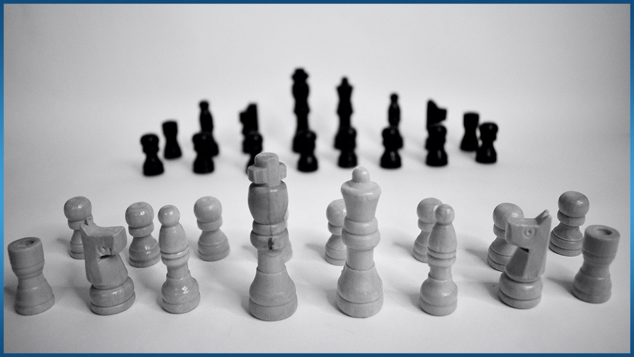 black and white chess pieces facing each other