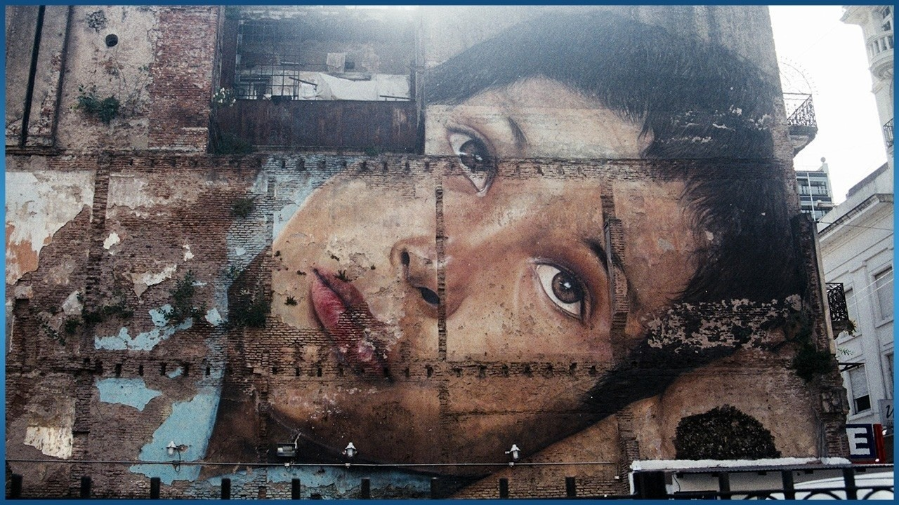 painting of woman on brick wall