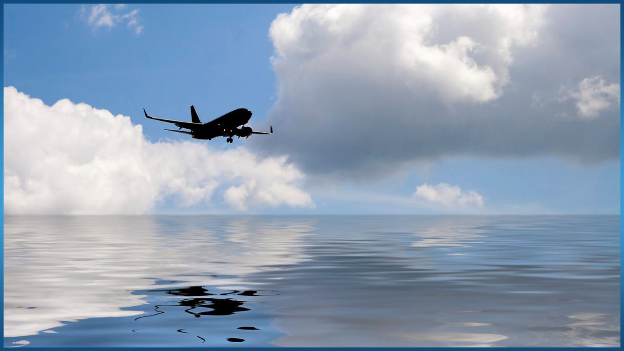 plane flying low over ocean