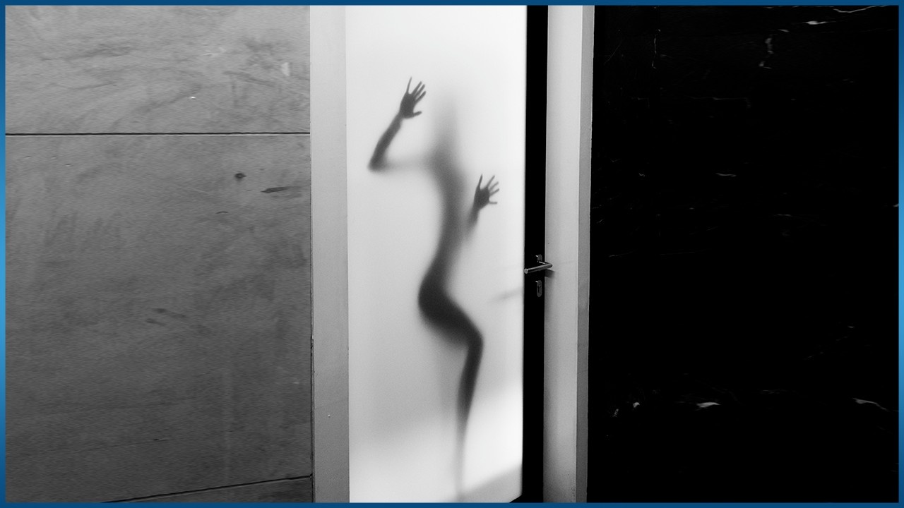 naked female figure standing behind glass
