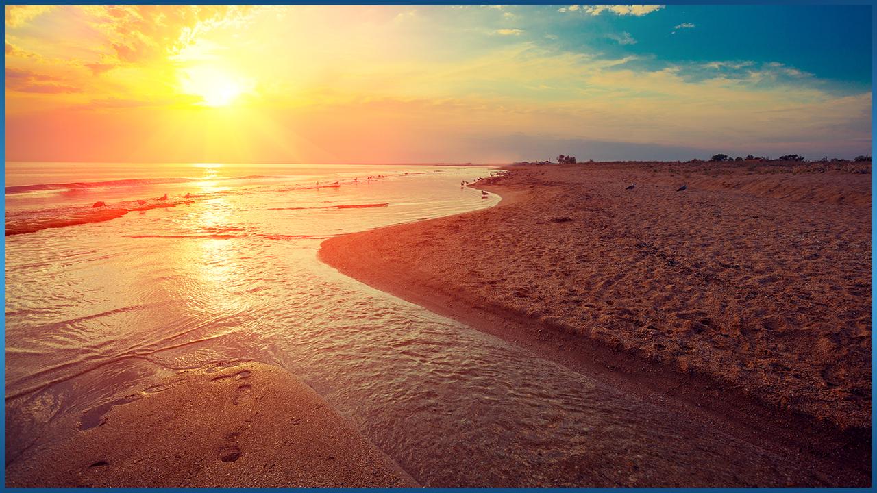 sun setting over beach