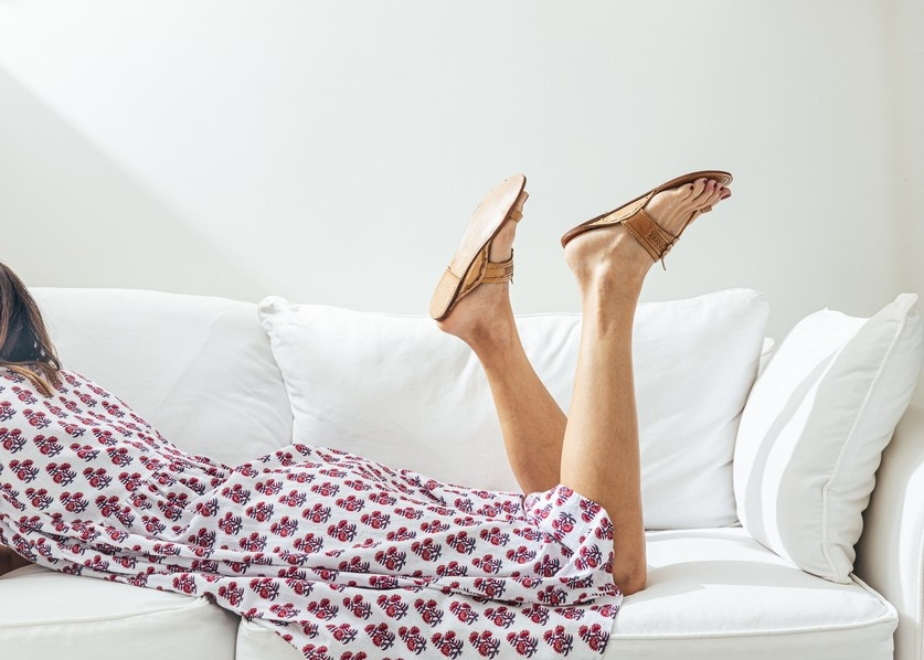 female entrepreneur takes a break mid-day and reclines on the couch, feet in air, experiencing joy
