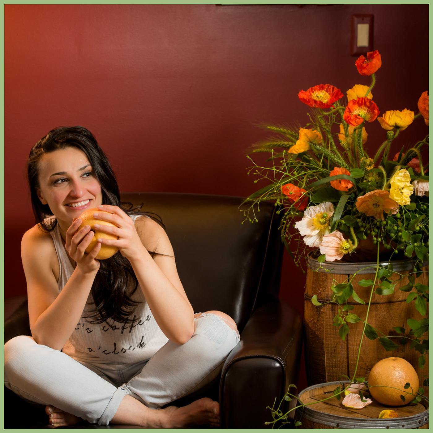 girl seating on a armchair holding a grapefruit next to poppy flower arrangement Viva La Flora Live Podcast