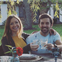 female has her arm around a male and they are sitting down outside at a table