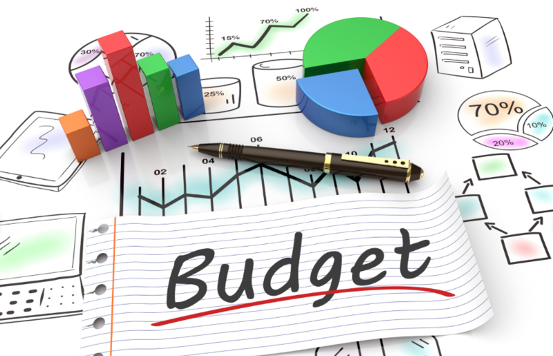"""The word """"Budget"""" written on a piece of paper, a pen, bar and pie chart"""