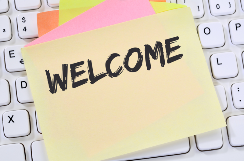 Welcome written on a yellow sticky note on a computer keyboard