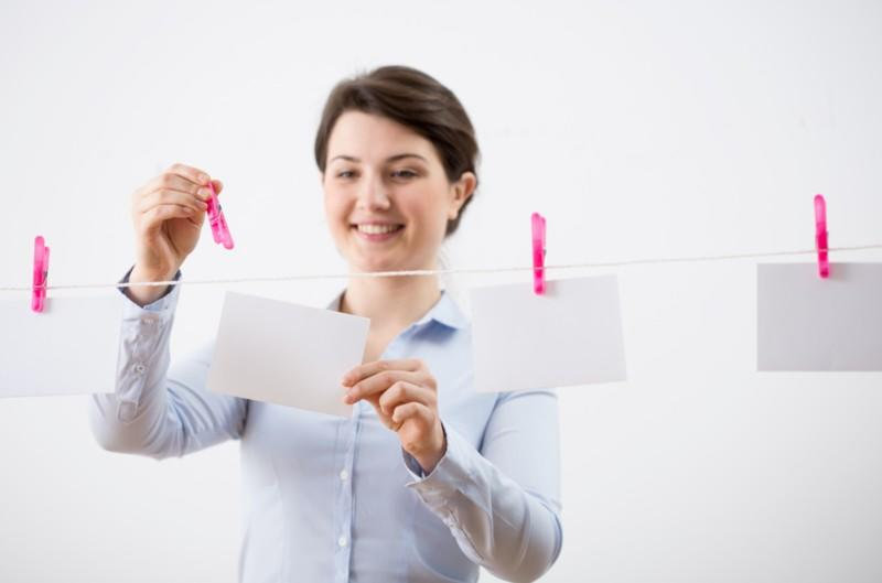 smiling woman clipping flashcards on a white rope with pink clothing pins