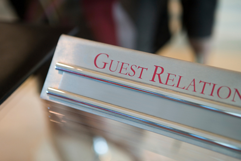 """silver binder with """"Guest Relations"""" written on it it in cranberry colored letters"""